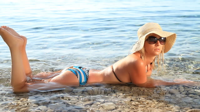 stockvideo's en b-roll-footage met hd: sexy woman relaxing in shallow water - op de buik liggen