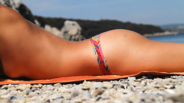 hd: sexy woman sunbathing on the beach - sunbathing stock videos and b-roll footage