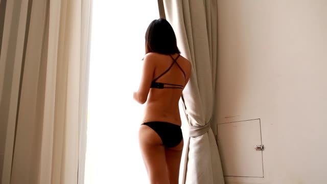 stockvideo's en b-roll-footage met sexy woman walk across the room - huis interieur
