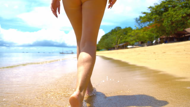 slo mo sexy woman walking along tropical beach - bali stock videos & royalty-free footage
