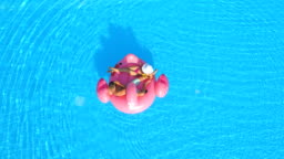AERIAL: Sexy young couple sipping cocktail drinks on pink flamingo float in pool