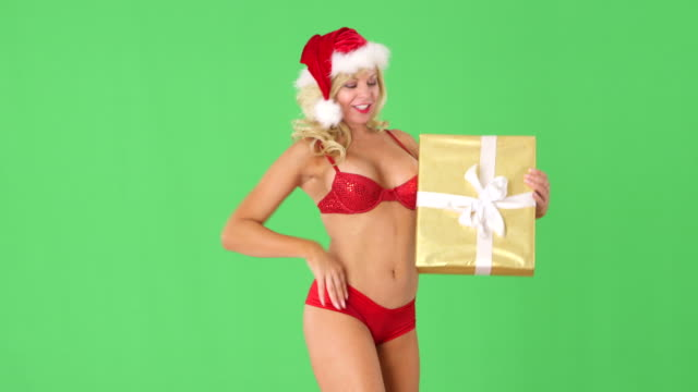 sexy young girl in santa hat with present and blowing kisses - santa hat stock videos & royalty-free footage