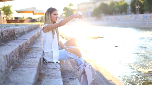 Sexy young stylish hipster woman posing and taking selfie