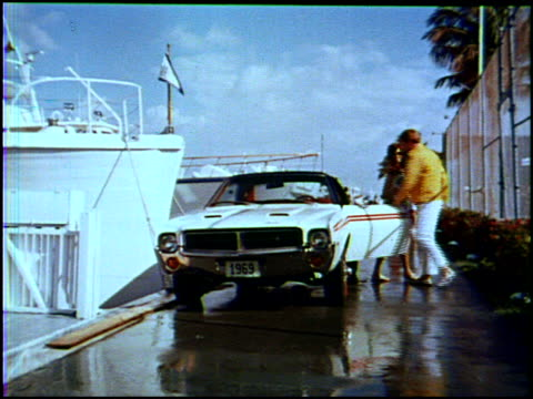 vídeos de stock, filmes e b-roll de sexy young woman in a green, see-through mini skirt pulls up to a boat at the marina. she's driving her 1969 amc javelin sst. all her swinging... - 1960 1969