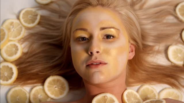 Sexy young woman lying on a bed of lemons