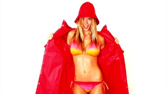 vidéos et rushes de sexy jeune femme portant un manteau - bikini