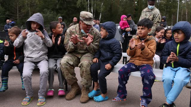 sgt. michael daniels of the u.s. army, who has become immensely popular with afghan evacuee children, sits with some of them while listening to an... - us military stock videos & royalty-free footage
