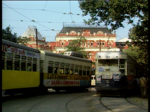 shabby trams passing in street ornate brick building behind india - 1986 stock videos and b-roll footage