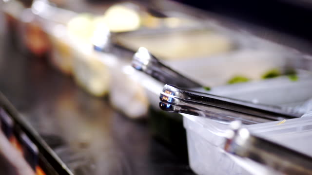 Shabu buffet trays with tongs for self service in the restaurant.