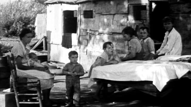 vídeos de stock, filmes e b-roll de shack or shanty house / bed outside shack / mother and children sitting outside shack / woman folding blanket on bed outside / father and mother... - 1933