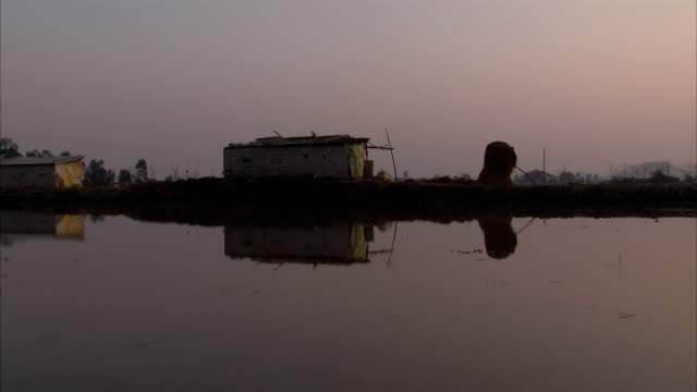 shacks on a lakeshore reflect on the surface of the water. - seeufer stock-videos und b-roll-filmmaterial