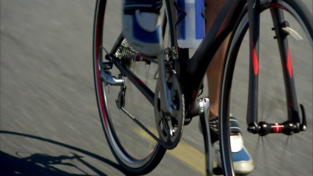 vídeos y material grabado en eventos de stock de ts cu pan shadow and feet of woman cycling on road / strandfontein, western cape province, south africa - triatleta
