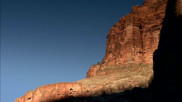 a shadow falls across a sandstone cliff in the grand canyon. - sandstone stock videos & royalty-free footage