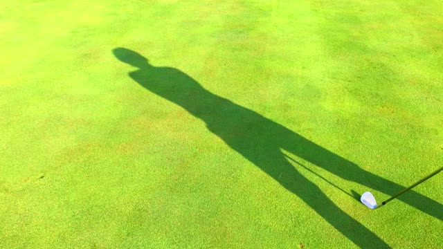 shadow golfer making a golf swing on the grass - golf swing silhouette stock videos & royalty-free footage