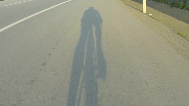 Shadow hitting the road on the sunset bicycle ride