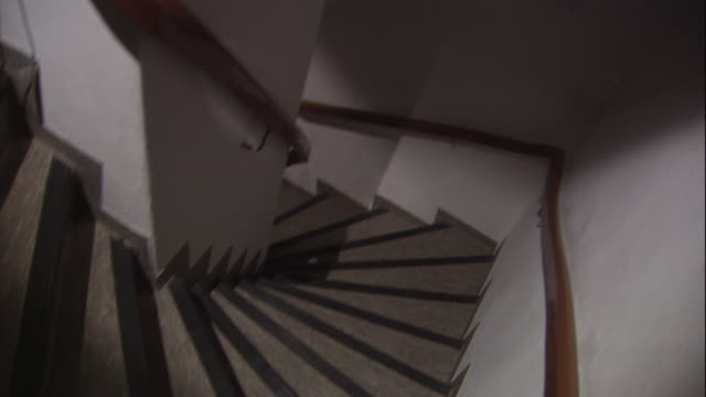 a shadow moves down a spiral staircase. - spiral staircase stock videos & royalty-free footage