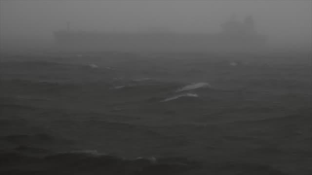 vídeos de stock, filmes e b-roll de sombra de um barco de carga que navegam em um mar agitado - navio