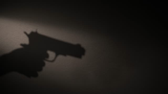 a shadow of a hand holding a gun in his hand. - sparare video stock e b–roll