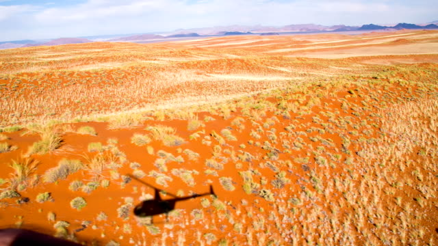 aerial shadow of a helicopter in namibian desert - namibian desert stock videos and b-roll footage