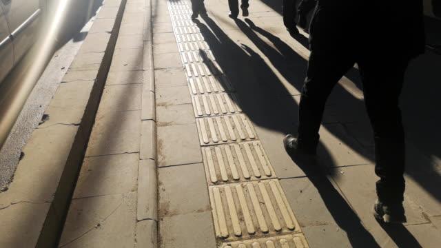 vidéos et rushes de ombre d'un homme sur le trottoir patterened - silhouette
