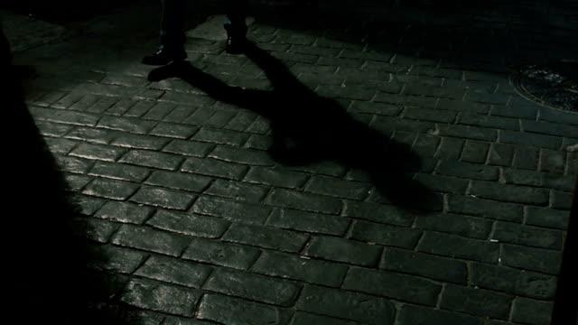 Shadow of a man walking on cobblestone way