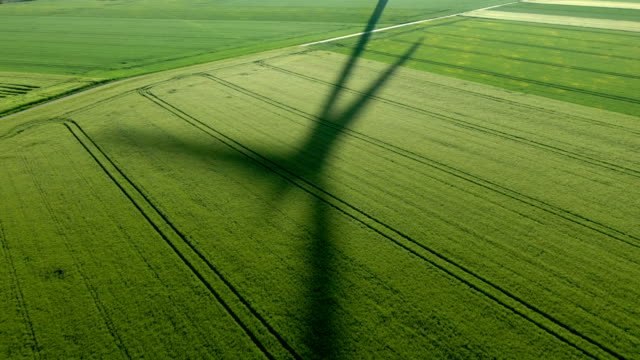 shadow of a wind turbine on a field - environmental conservation stock-videos und b-roll-filmmaterial