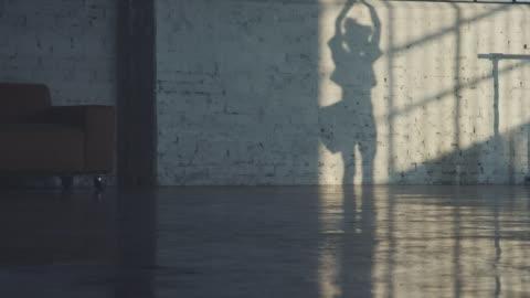 vídeos y material grabado en eventos de stock de sombra de bailarina girando sobre pared de ladrillo - sombra
