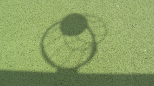 shadow of basketball thrown into hoop with green floor background - spielball stock-videos und b-roll-filmmaterial