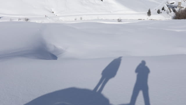 Shadow of couple on snow, tilt up to village