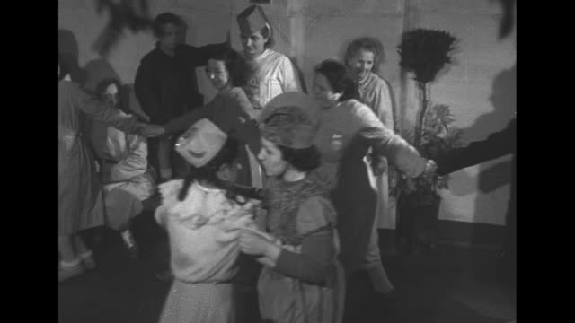 vídeos de stock, filmes e b-roll de shadow of dancing people on a wall decorated with a garland with a pan down to expressionless people seated on a bench / a group of uniformed nurses... - preto e branco