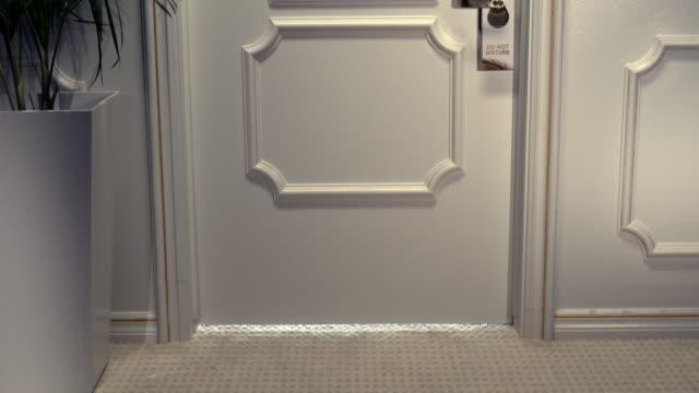 """shadow of footsteps under door, reveals hotel door with """"do not disturb"""" sign - under her feet stock videos & royalty-free footage"""