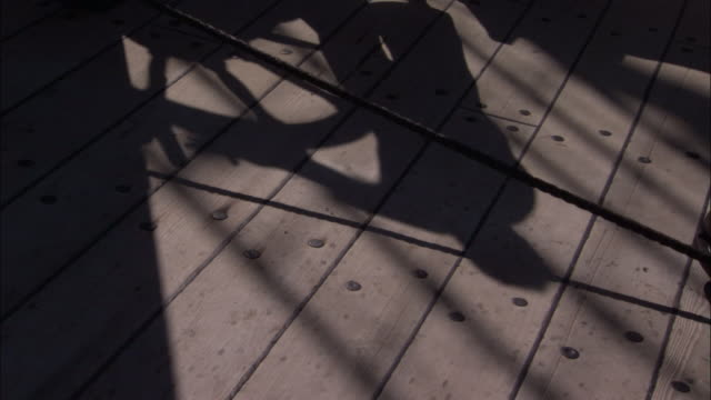 Shadow of helmsman on replica of HMS Endeavour.