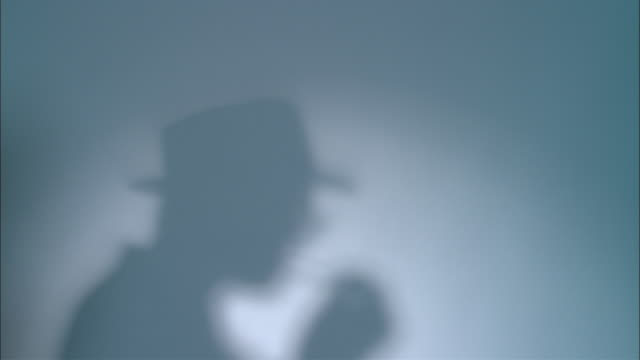 ms shadow of man on wall of man in hat lighting cigarette/ man dressed in 1940's suit and hat walking on  looking at camera  and walking off/ new york city  - film noir style stock videos and b-roll footage