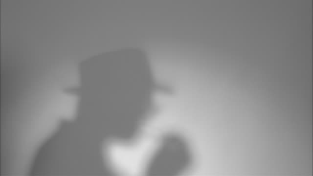 b/w ms shadow of man on wall of man in hat lighting cigarette/ man dressed in 1940's suit and hat walking on  looking at camera  and walking off/ new york city  - detektiv stock-videos und b-roll-filmmaterial
