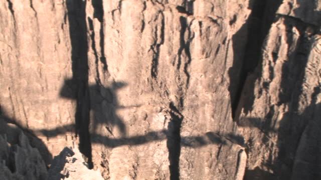 vídeos de stock e filmes b-roll de cu, ha, pan, shadow of person crossing rope bridge on limestone rock formations in tsingy de bemarha national park, madagascar - ponte suspensa