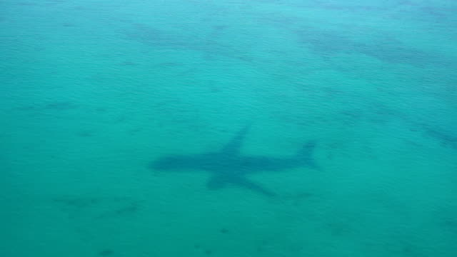 shadow of the airplane on the sea background - air vehicle stock videos & royalty-free footage