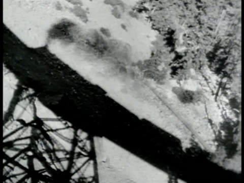 td ws shadow of train on rural landscape below landbridge la tu ws train of flatbed cars w/ military trucks moving on land bridge tracks wwii world... - 1943 stock videos & royalty-free footage