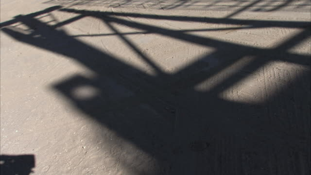 vídeos de stock, filmes e b-roll de cu shadow on the sandy ground of an oil well pumping / bakersfield, california, united states - sonda petrolífera