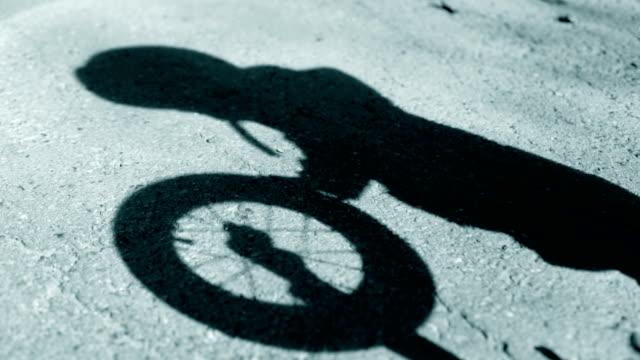 vídeos de stock, filmes e b-roll de criança joga sombra, bicicleta - sombra em primeiro plano