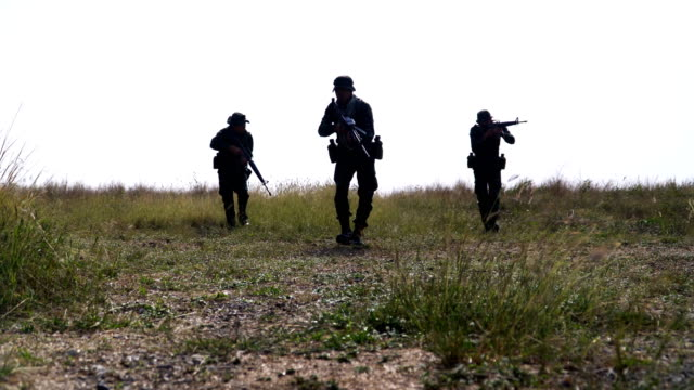 shadow shape of group of fully Equipped and Armed Soldier is patrolling on meadow