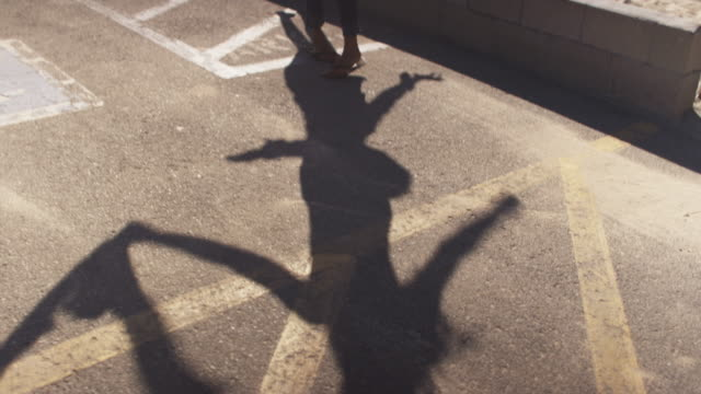 Shadows cast by two women spinning and dancing in sun of parking lot