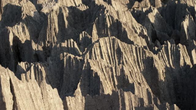 Shadows creep as sun drifts over eroded tsingy karst limestone rocks, Ankarana, Madagascar