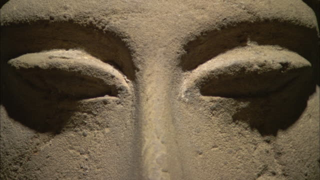 shadows define the eyes of a pitted ceramic face in luxor, egypt. - luxor stock-videos und b-roll-filmmaterial