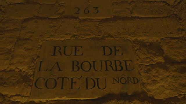 shadows disrupt orange artificial lighting highlighting an underground street sign reading 'rue de la bourbe cote du nord' paris france fkax912p clip... - claustrophobia stock videos & royalty-free footage