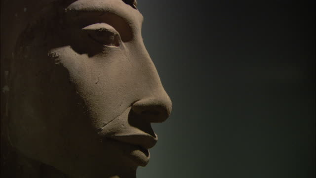 Shadows emphasize the prominent cheekbone of an ancient carving of a face in profile.
