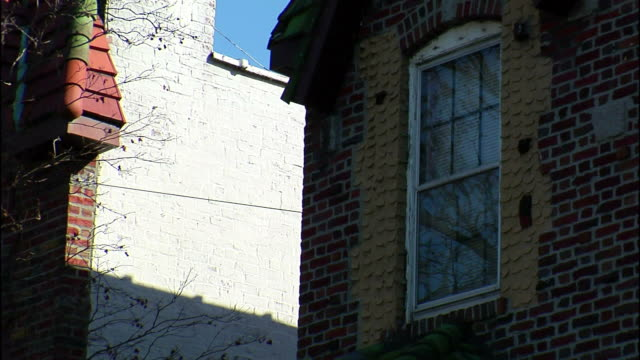 shadows fall across a brick house with a single window. - brick house stock videos & royalty-free footage