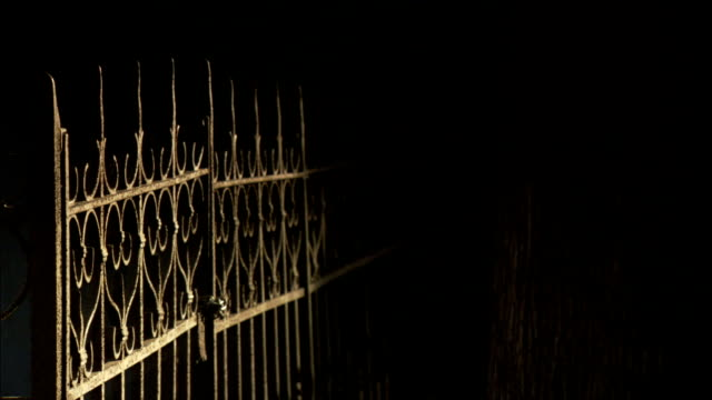 Shadows fall across a decorative wrought iron gate and a pillar in the Monumental Cemetery of Staglieno. Available in HD.