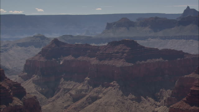 shadows fall across the uppermost walls of the grand canyon. - canyon stock-videos und b-roll-filmmaterial
