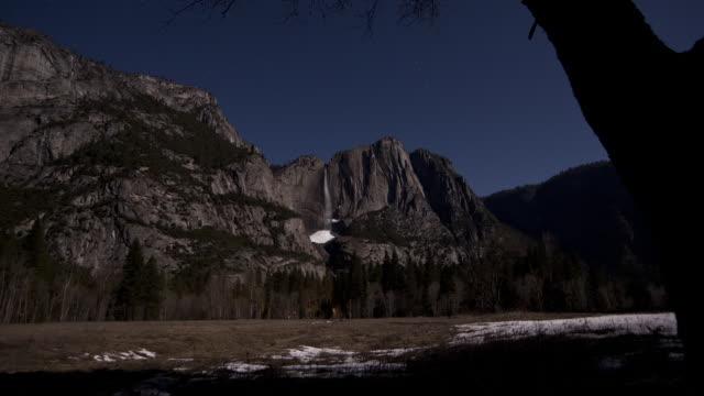 Shadows move in bright moonlight near the Yosemite Falls in the Yosemite Valley of Yosemite National Park.