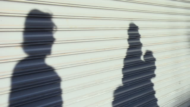 MS, Shadows of people passing by shuttered store window, Seattle, Washington, USA